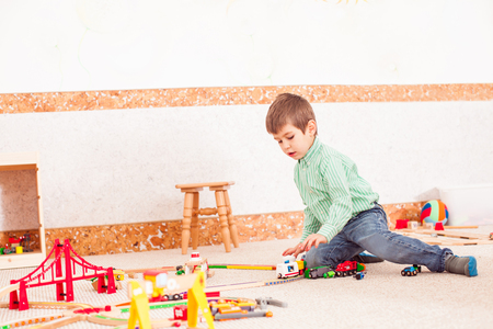 wood railways: Boy playing with toy  road Stock Photo