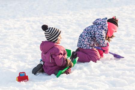 아이들은 눈 위에서 놀다.