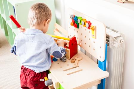Menino brinca com brinquedos de madeira Foto de archivo