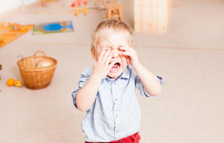 crying little boy in the kindergarten