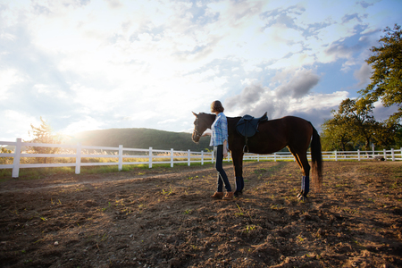 A young woman riding a horse looks at the sunset