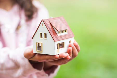 The girl holds a small house in her hands. The conception of adoption