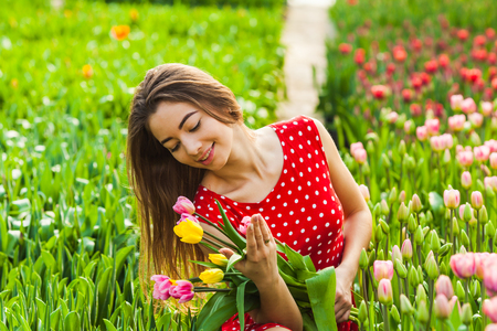 Beautiful woman with colourfull tulips Фото со стока