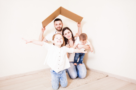 Young father holding cardboard roof upon his family