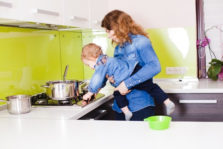Mom with her 1 year old child cooking