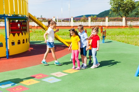 Children learn to play hopscotch in the summer outdoors