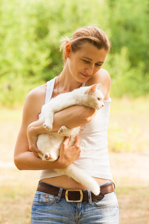 Woman petting her lovely cat during summer city walk