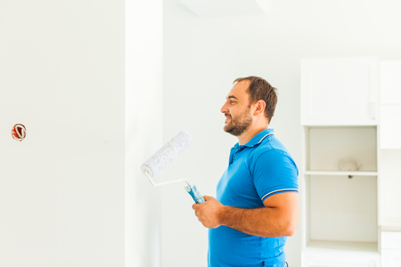 Young smiling painter looking at whitewashed wall
