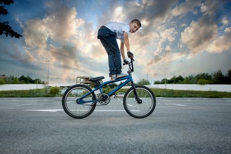 Vista ravvicinata del giovane motociclista che fa acrobazie spericolate in bici