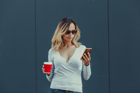 Woman with red coffee cup and smartphone Stock Photo