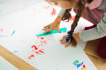 Girl painting with her fingers on a large sheet of paper