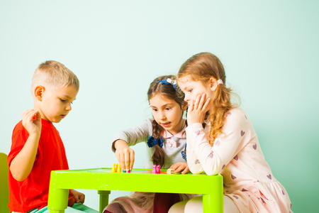 Kids playing board games sitting at the table