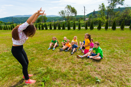 Happy kids guessing during charades game at summer camp