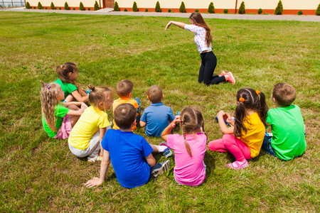Back view of children spending time outside and playing charades