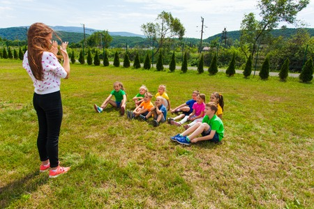 Kids playing charades outdoors in the summer camp