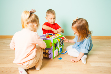 Amazing busy cube and three kids playing with it Stock fotó