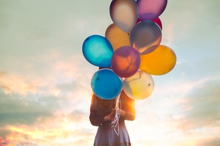 Teenage girl holds a bunch of balloons before face 版權商用圖片