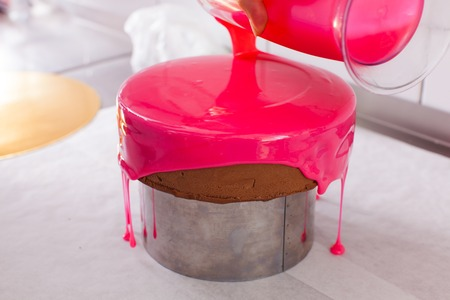 Process of decorating cake with mirror glaze Standard-Bild