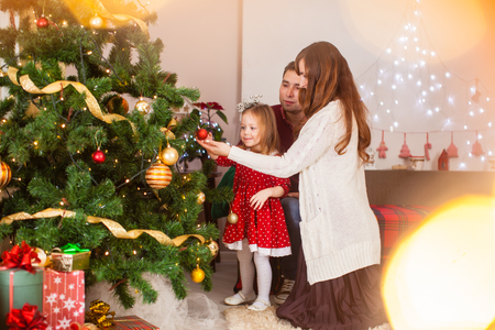 Happy family with daughter decorate Christmas tree 스톡 콘텐츠
