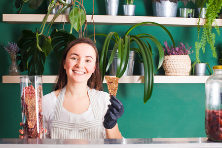 Young smile woman shows dehydrated crisps in vegan shop