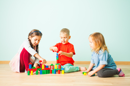 Young kids constructing towers from wooden blocks