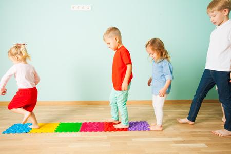 Kids barefoot stand in a row between massage mats Standard-Bild - 114857886