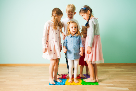 Group of kids stands on massaging mats