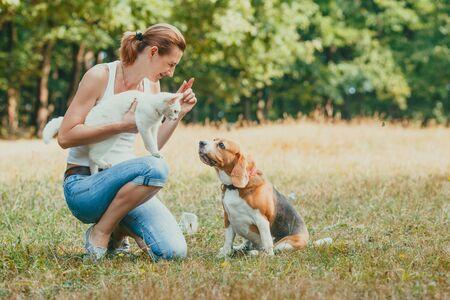 Pet owner kneeling hoding her cat and training her dog Banque d'images - 130092217