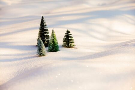 Small artificial christmas trees on soft snow