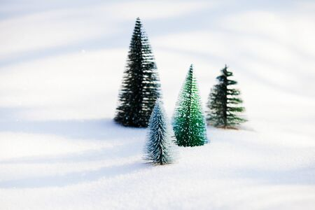 Green artificial christmas trees on untouched snow