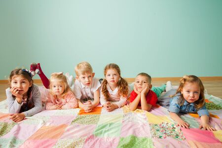 Group of six kids laying on the floor at home