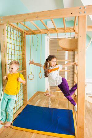 Niño y niña sonriente balanceándose en el complejo deportivo