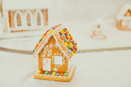 Gingerbread cookie house in the Christmas village on the fair. Holiday traditional aroma dessert with honey and spices
