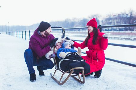 Beautiful young couple near their kids, sitting on sleigh. Lovely girl and cute boy muffled in warm cover on wooden sleigh with their parents sitting near. Snowy city view on background