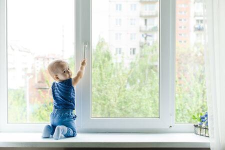 Kleiner Junge auf der Fensterbank, Gefahr im Haus
