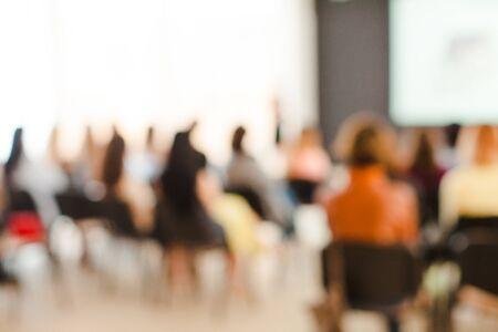 Gente borrosa sentada en las sillas en la conferencia y presentación en la sala de conferencias. Actuación de arte