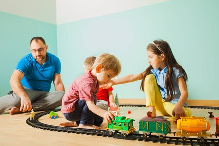 Father and his children play with a toy railway on the floor