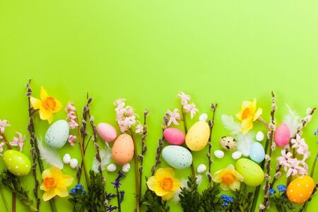Holiday Easter concept. Green Easter background with eggs and wilow branches and spring flowers a border with place for text.