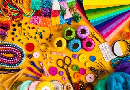 Bastelbedarf zum Stricken und kreative Handarbeit auf Gelb. Draufsicht auf das Set. Organisieren von DIY-Elementen, Bordürendesign