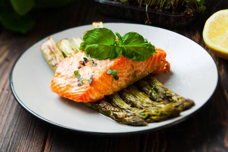 Grilled salmon and asparagus on the white plate. Backed fish fillet with green asparagus, healthy food close up Stockfoto - 130093777