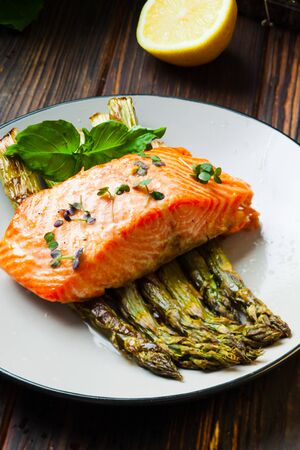 Healthy food - peace of salmon, backed with asparagus with lemon souce on the table Stockfoto - 130093851