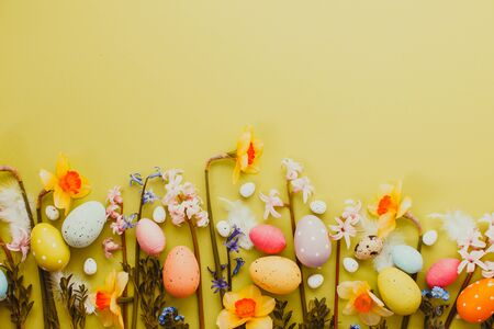Easter background with Easter eggs and spring flowers on yellow background. Top view with copy space