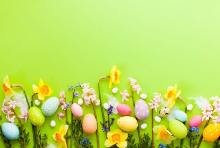 Easter background with Easter eggs. Beatyful Easter spring flowers over green background with place for text