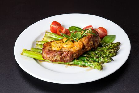 Gourmet steak with green asparagus. Concept for a tasty and healthy meal. Close up.