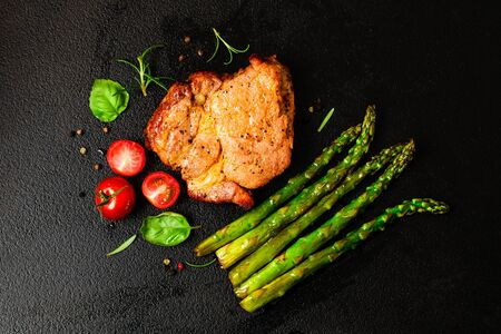 Barbecue grilled beef steak meat with asparagus and tomatoes. Top view on black background Фото со стока