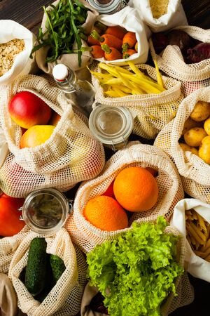 Zero waste food shopping. Fruits and vegetables in cotton bags, oil and spices in glass jar. Top view