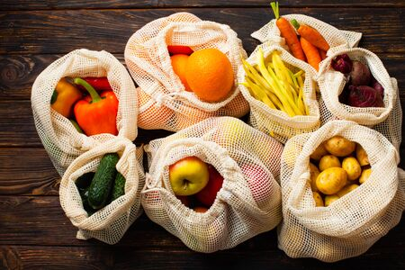 Vegetables in eco organic cotton bags top view. Zero waste food shopping. Фото со стока