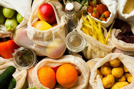 Vegetables and fruits in textile bags, glass jars with beans and oil as a background. Zero waste food shopping. Фото со стока