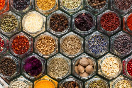 Herbs and spices in open glass jars, top view like a honey comb. Diversity of condiments Imagens