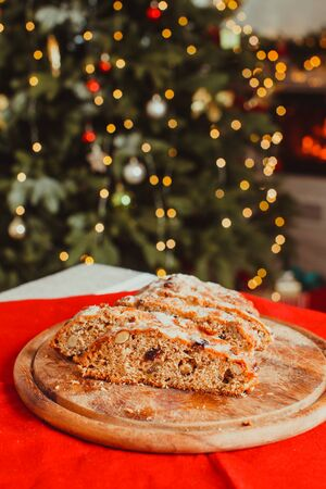 Christmas Stollen. Traditional Sweet Fruit Loaf with Icing Sugar. Xmas holiday table with stollen. Christmas tree and burning fireplace in the room on the background Standard-Bild